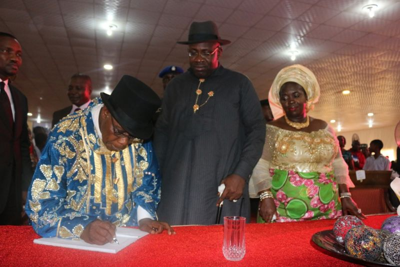 Former President, Chief Olusegun Obasanjo (left) signing the visitors registrar shortly after an interactive session with students of the Ijaw National Academy during his 3-day visit to Bayelsa State to commission several landmark projects, as part of activities to mark the Restoration Government's 6th year anniversary celebrations at Kaiama in Kolokuma/Opokuma Local Government Area of the State, while the Governor of the State, Hon. Seriake Dickson (centre) and his wife, Rachael (right) look on.