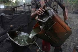 •A worker pours crude oil into a locally made burner
