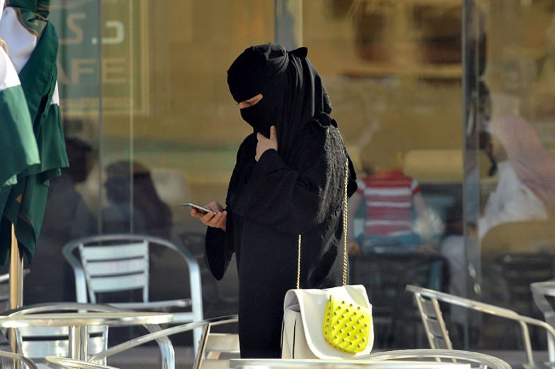 •A Saudi woman looks at her mobile phone in the capital Riyadh