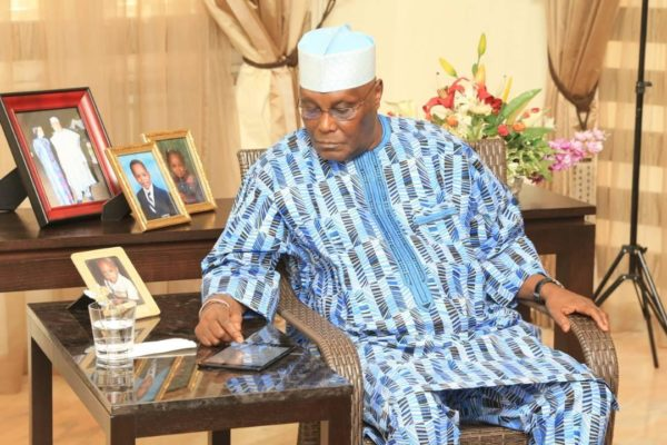 •Atiku fiddling with his smartphone during the live broadcast