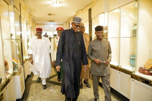•President Buhari being escorted by Vice President Osinbajo.