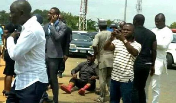 •Senator Dino Melaye on the ground after allegedly jumping from a police vehicle, Tuesday in Abuja