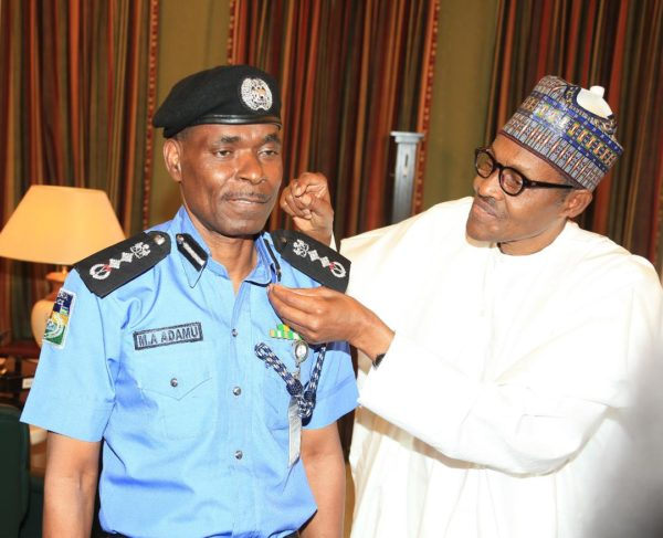 •President Buhari decorating IGP Mohammed Adamu with his new rank. Photo: NAN.