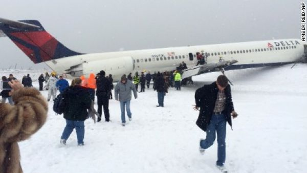 •Trapped in snow: Passengers of the Delta airline making their way out of the snow-trapped plane.