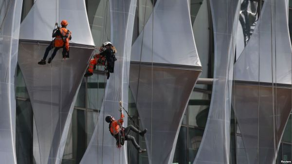 •Construction workers – potential slaves – climbing a new building in London, Britain.