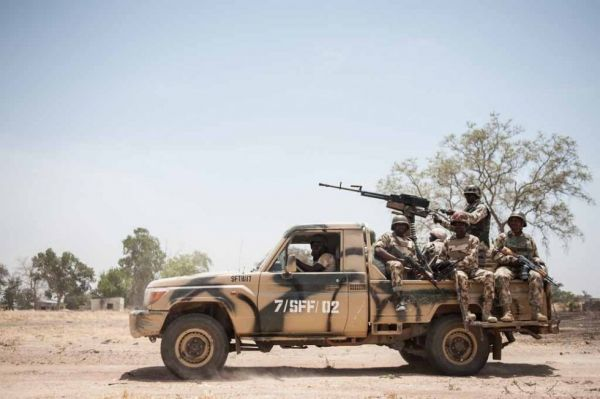 •Nigerian soldiers sit on a military pick-up truck at a military base.